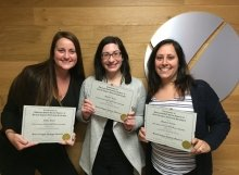 group of 3 recieve their certification in front of their company logo in the lobby