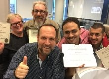 Four happy students with their SEO Certification Diplomas pose for a fun selfie with Greg